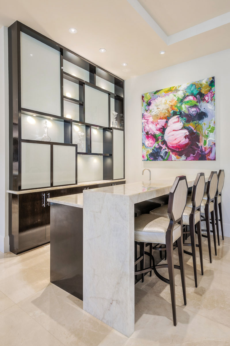 In the bar area, a focal wall once again takes center stage with a Mondrian-inspired, puzzle-like display of square shelving. In octagonal complement, Tomlinson stools pull up to a Cristallo Extra Quartzite waterfall bar. A vibrant painting, Bel Canto by artist Carmelo Blandino, brings a sense of playfulness to the otherwise geometric space.