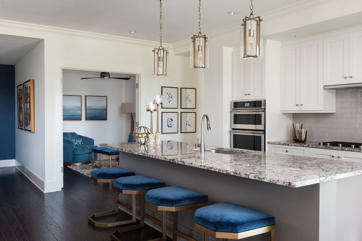 CR Laine's blue chenille velvet splashes on to the cushions of the lightweight, unusually shaped hexagonal bases of CTH Sherill Occasional counter stools tucked beneath the island. Gabby Home's trio of lanterns glow with modern attitude above, while Paragon Picture Gallery's four watercolor giclées add an artistic touch.