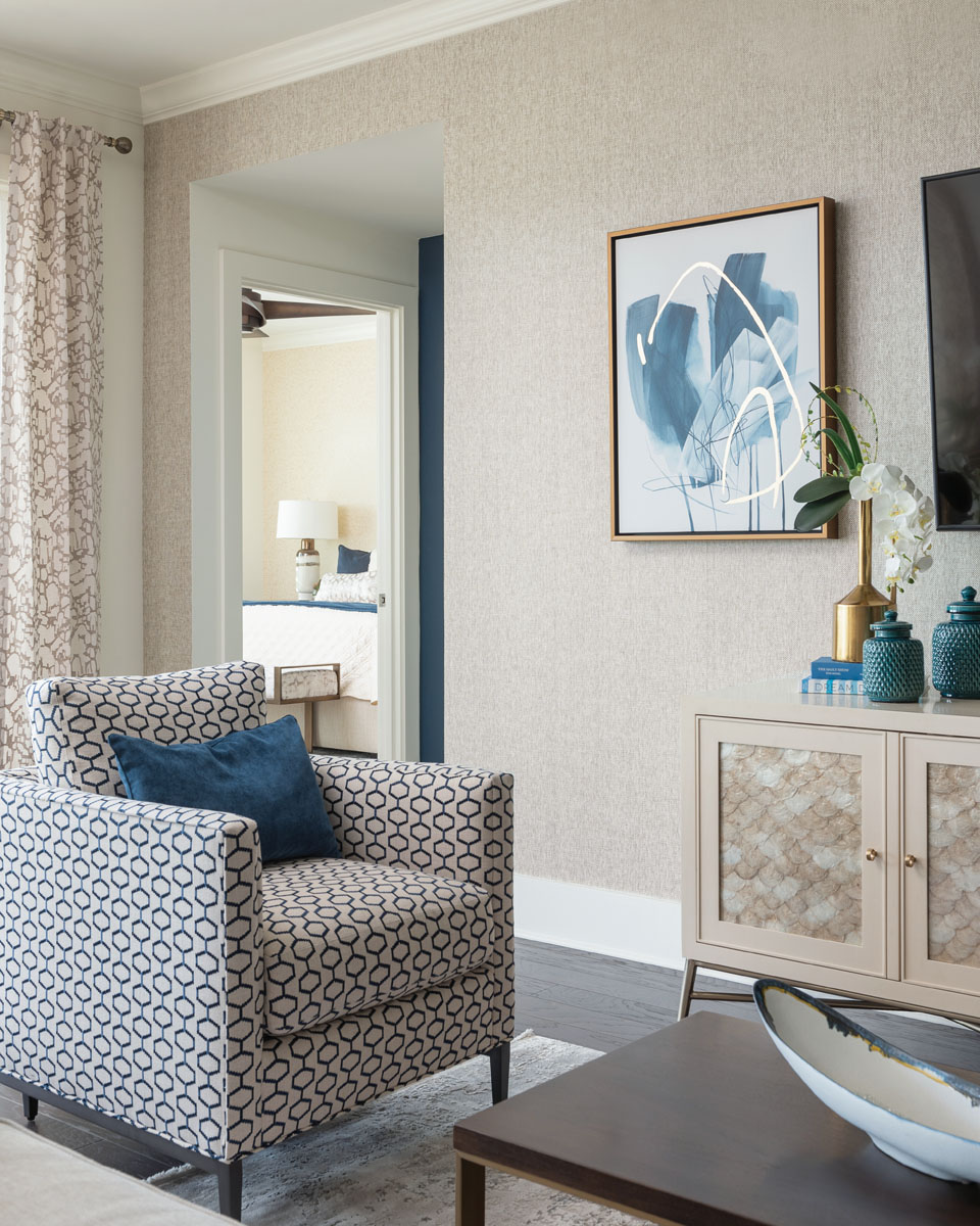 Shimmering, scalloped capiz shells style the front of Bernhardt's cabinetry that lines the wall of the living area. Here, artist Janice Sadler's Neutral Blooms II from Leftbank Art gives a creative nod to the waves of blue that splash throughout the home.