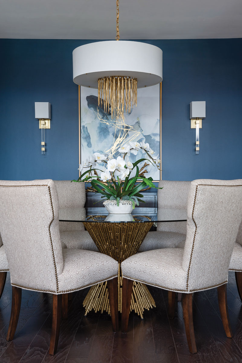 """Wayward II, a giclée by artist Emma McCartney, continues the color conversation in the dining area, where Currey & Company's dramatic drum chandelier circles above Ambella Home's """"Pick Up Sticks"""" table topped in glass."""