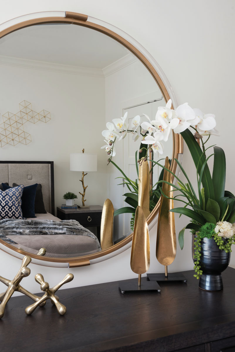 """Forged in iron finished in gold leaf and framed in a rim of acrylic, the contemporary stylings of Uttermost's """"Mackai"""" mirror reflects the charming design elements in the guest room."""