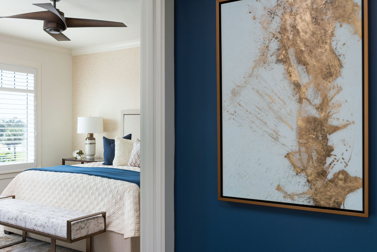 Minka-Aire's dark wood fan balances the light and airy master bedroom, where a custom bench with a metallic thread running through it abuts the simple bed from Bernhardt.