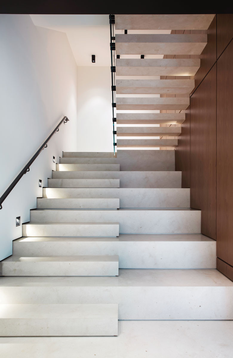 In complement to the home's minimalist organic architecture, a natural limestone stairway exudes a simple elegance as a visually compelling structural work of art that appears to float midpoint.
