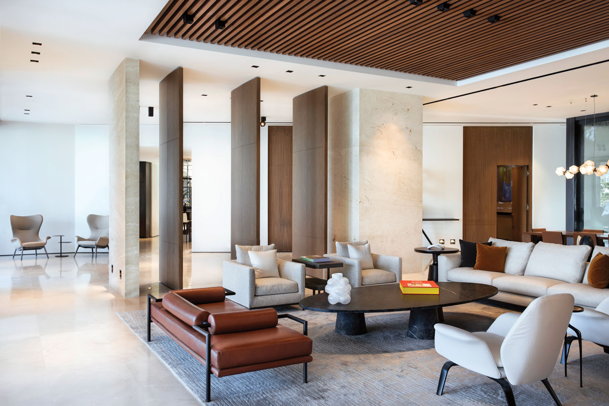 """The living room's natural materials, such as walls clad in travertine and limestone flooring, exemplify the modern architectural style of the home. Walnut accents offer warmth in complement to Minotti's seating ensemble and a black-framed """"Dorcia"""" daybed by Jorge Arturo Ibarra. Artefacto's sleek """"Bramare"""" lounge chairs corner the space beyond."""