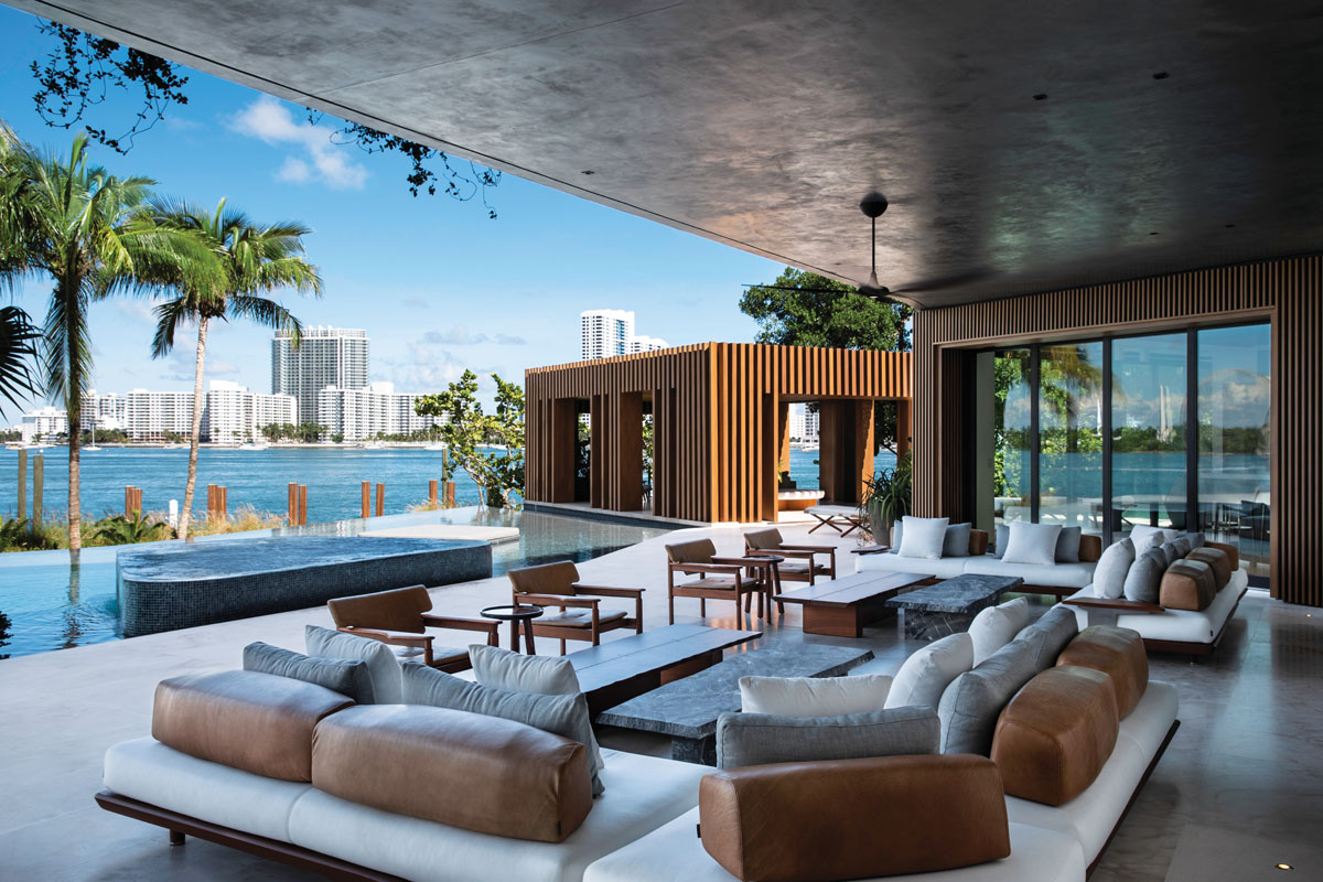 The ultimate hangout, this main-floor loggia is generously furnished with comfortably cushioned outdoor seating from Exteta that overlooks the mosaic glass-tiled pool. The cabana is surrounded by water and has direct access to the pool plus a beach entrance.