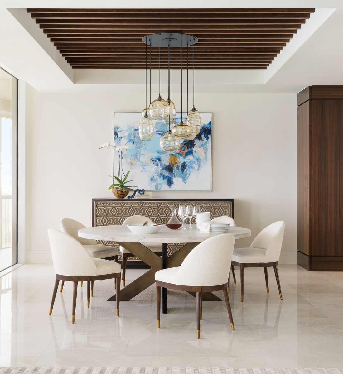 Modified barrel chairs swathed in off-white fabric circle the table topped in bleached burl wood complemented by the Alfonso Marina sideboard. The hand-carved wood piece is expressive and beguiling, while Wonder Clouds, adds a powerful splash of color above.