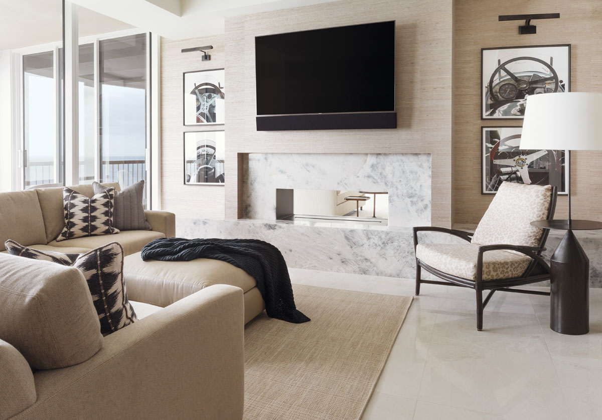 A photography collage of steering wheels from the Trowbridge Gallery adds panache to the den while echoing the black, taupe and off-white color scheme accented with the layered patterns of pillows. Kravet's oversized, cushy chenille-covered sectional is strategically juxtaposed hearthside.