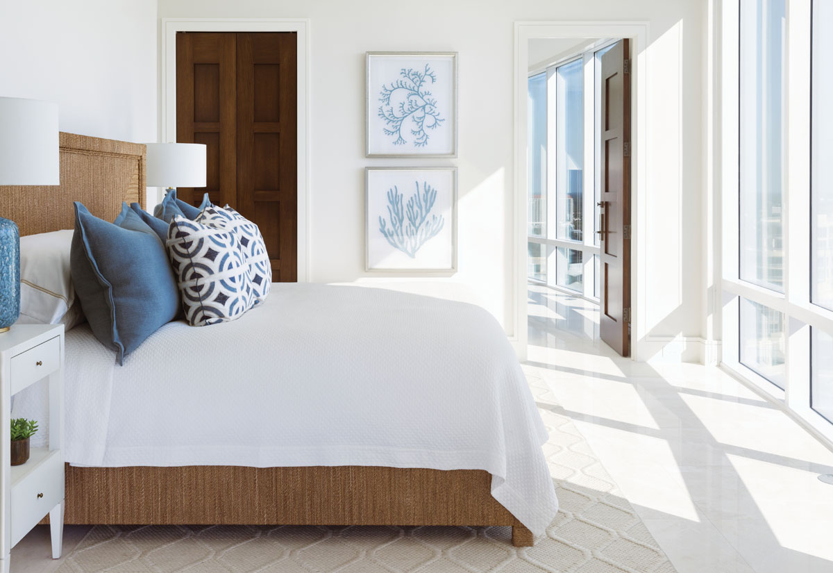 """Palecek's """"Decklin"""" rope-wrapped bed and a sisal area rug that bears a fashionable arabesque pattern infuses the guest room with texture. Organically inspired stacked art, """"Culloden Blue Lagoon"""" table lamps designed by Aerin Lauder for Visual Comfort, and accent pillows in shades of blue bespeak coastal chic."""