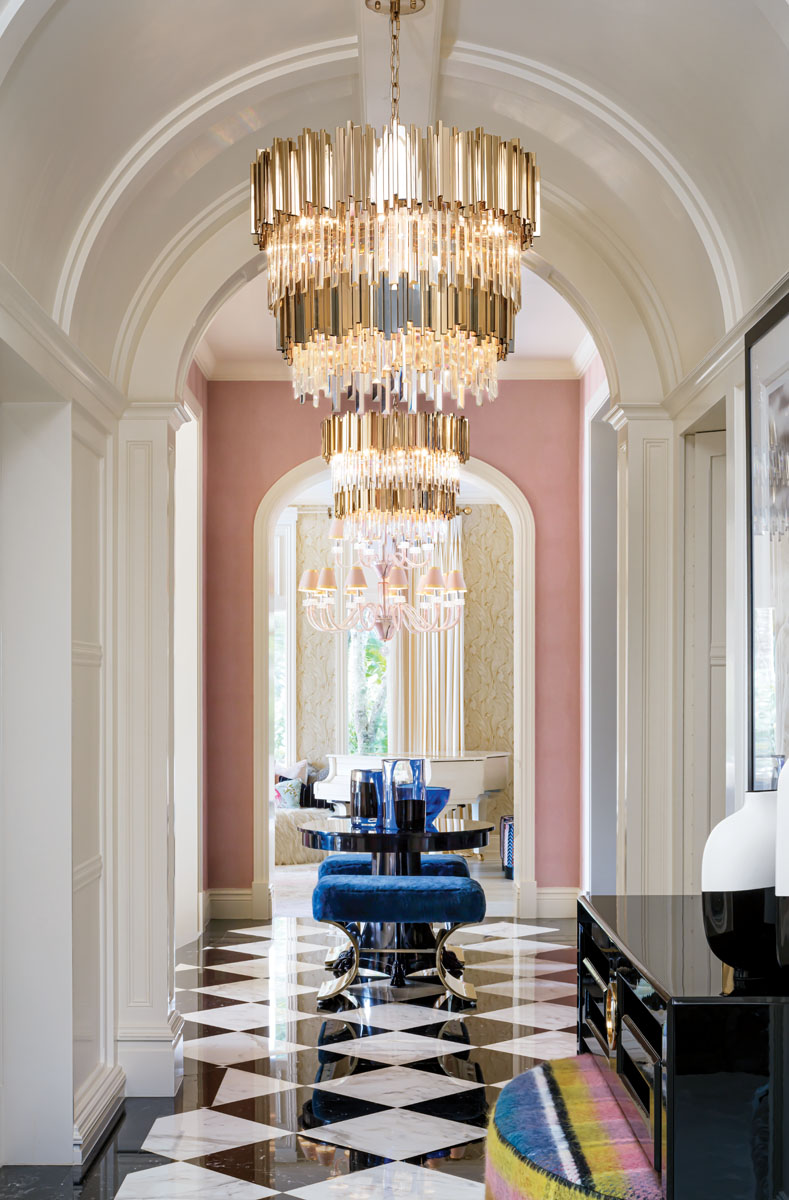 """Vaulted ceilings and carved moldings rise above the hallway in splendor as sumptuous velvets, brass, metals, glass and mirror dance. The House of LMD sets the tone for elegance with sleek Deco cabinetry and Ralph Lauren's """"Brook Street"""" gueridon table flanked by benches seated in a deep, royal blue."""