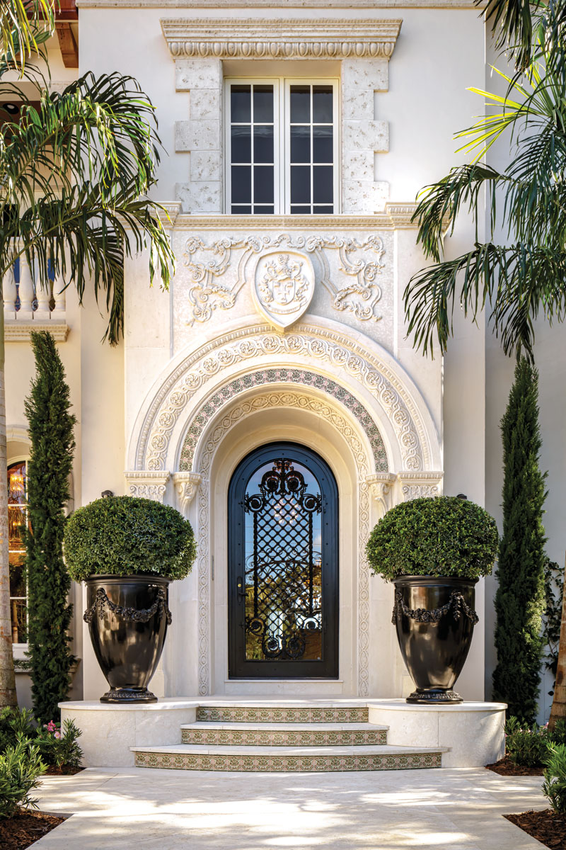 The front facade of this 12,500-square-foot manse utilizes massive urns and planters weighted against the new carved-limestone entry arch. Landscape architect John Lang's design adds to the theatrical approach where Morris' wrought-iron door beckons.