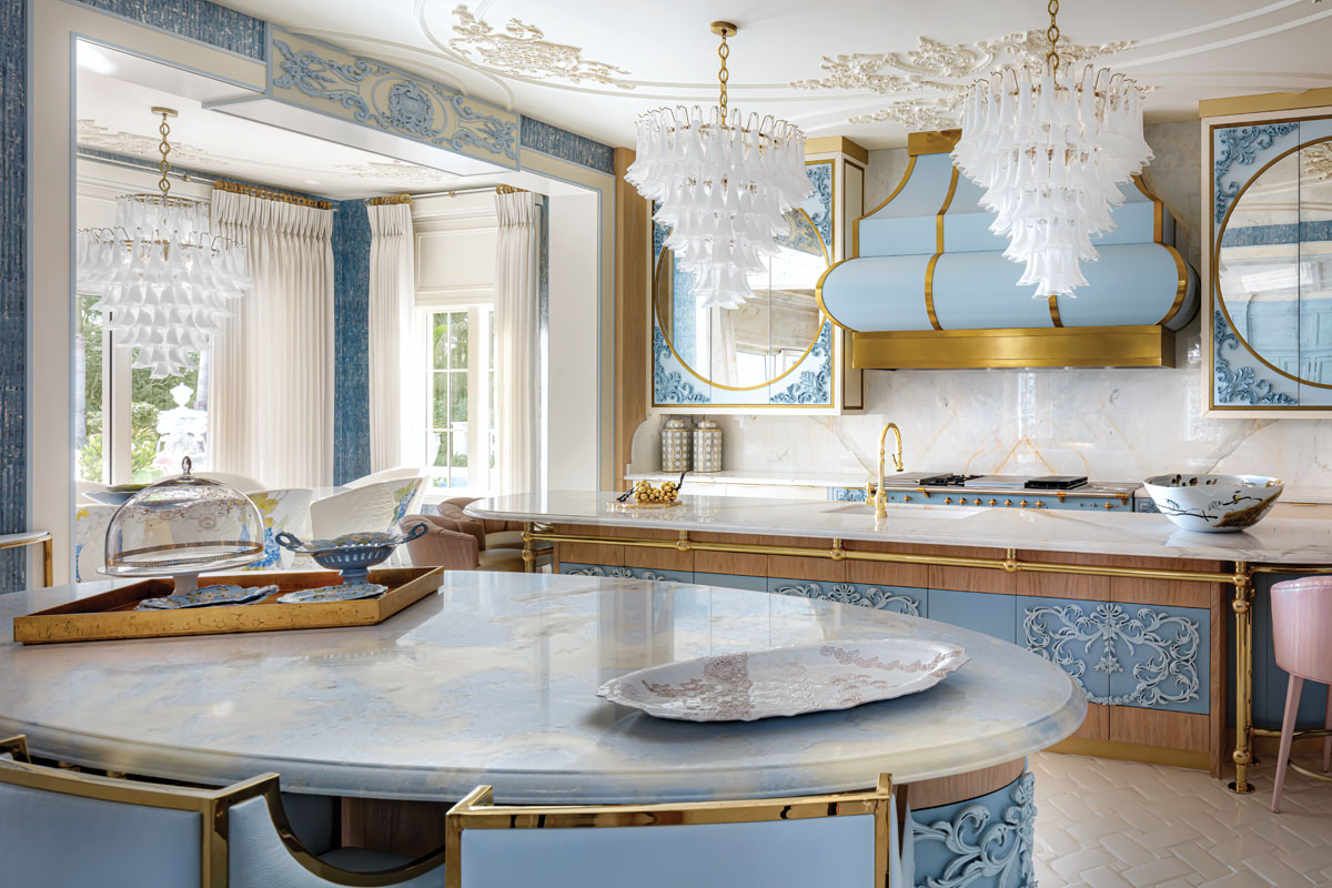 Carved tracery and an enamel-and-brass hood reminiscent of the Second Empire turn a mere kitchen into a sought-after venue. Overhead, curves and swirls in bas relief patterns resonate with an oval island, center prep station and mirrored cabinetry.
