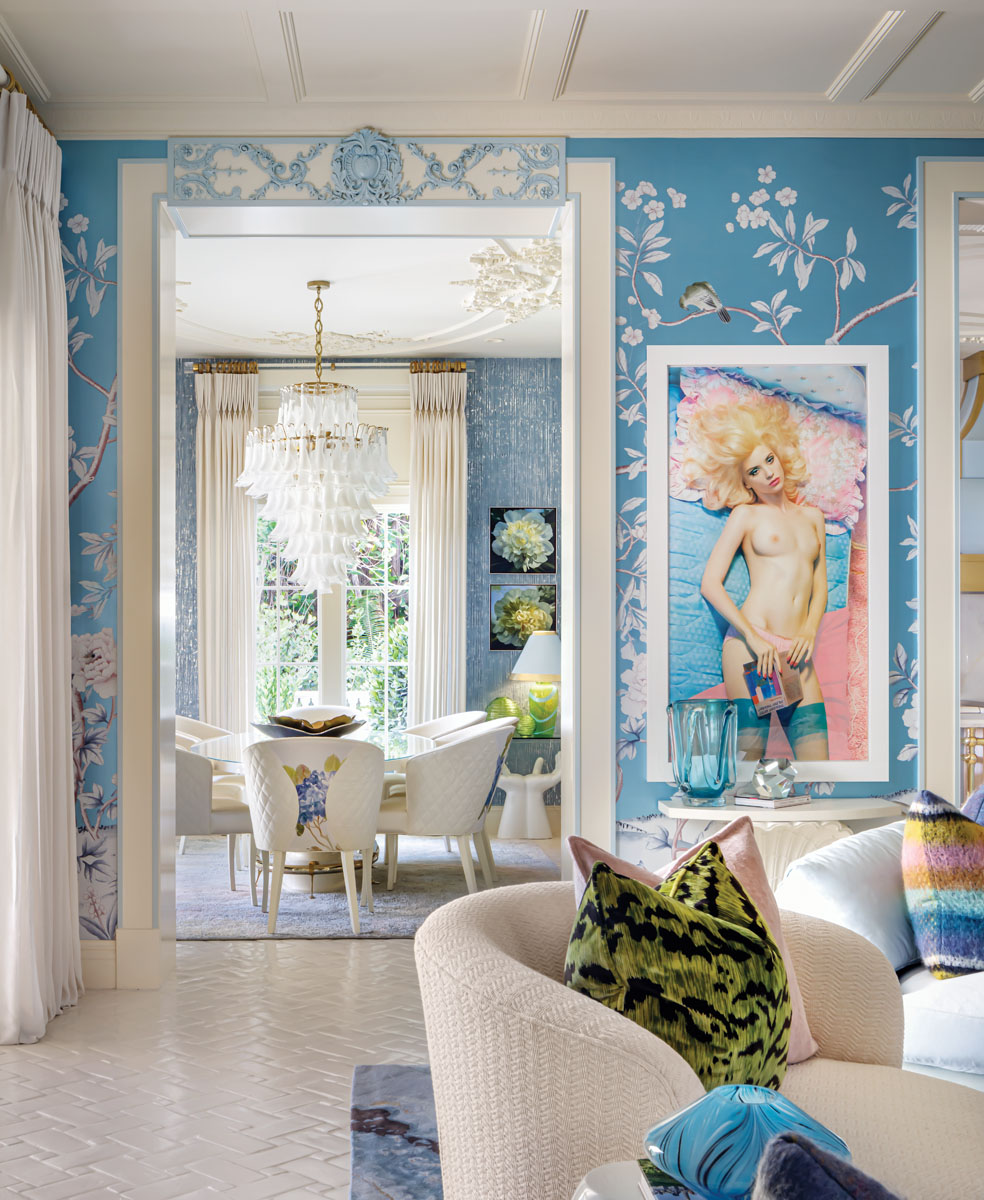 """The family room that sits just beyond the kitchen and breakfast area. Lee Jofa's chinoiserie wallcovering is the perfect foil for provocative wall art that is a signature of Morris' desire to offer """"smiles, sexiness and surprise,"""" all within a context that remains elegant and sophisticated. An Italian Murano glass chandelier draws the eye into the casual dining space."""