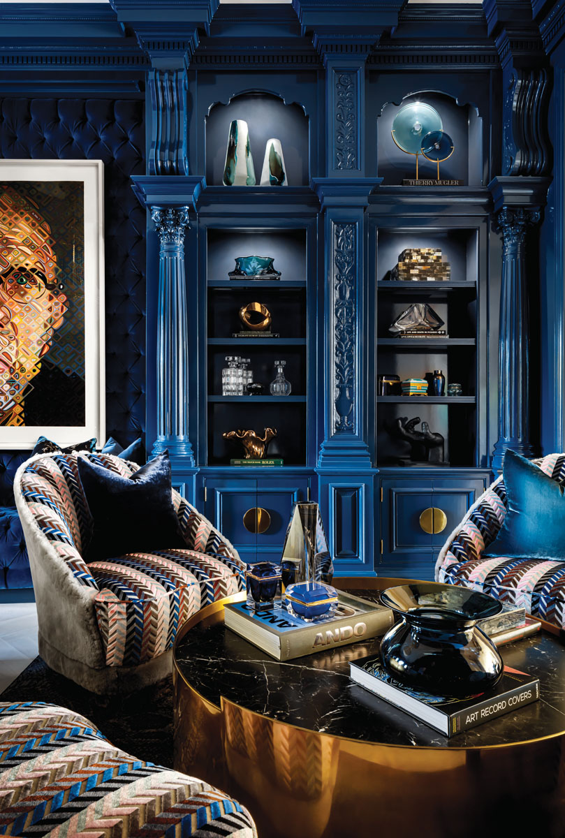 The masculine whiskey lounge is a perfect setting for conversation. Self Portrait 2017 by artist Chuck Close brings warm sienna and brown hues into harmony with custom LMD club chairs covered by Garrett Leather, Kelly Wearstler's brass cocktail table, and the matching pulls set against the cabinet's blue.