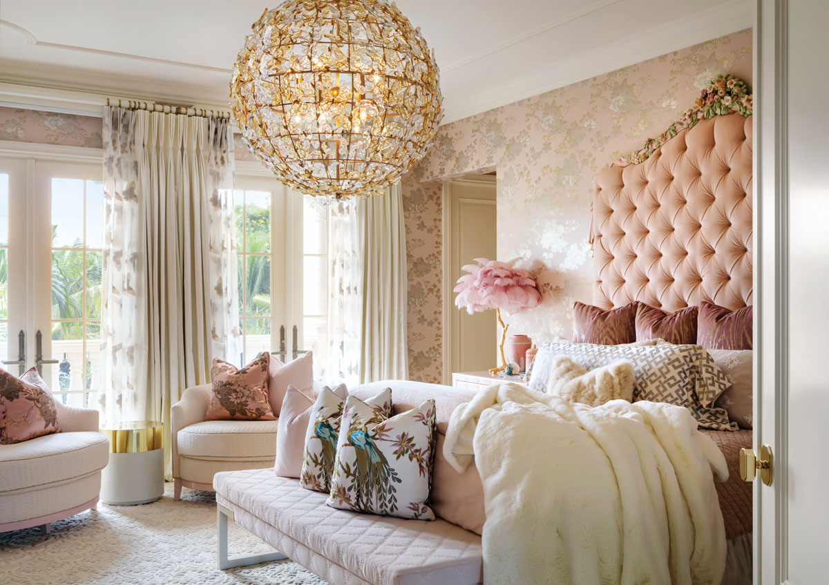 Corbett Lighting's crystal chandelier casts circles of light around the guest room that comforts with LMD's deft touches of elegance. Bedside, a fluff of pink feathers on a brass leg stands like a guardian ostrich. Delicately painted wallcovering completes the heady mix.