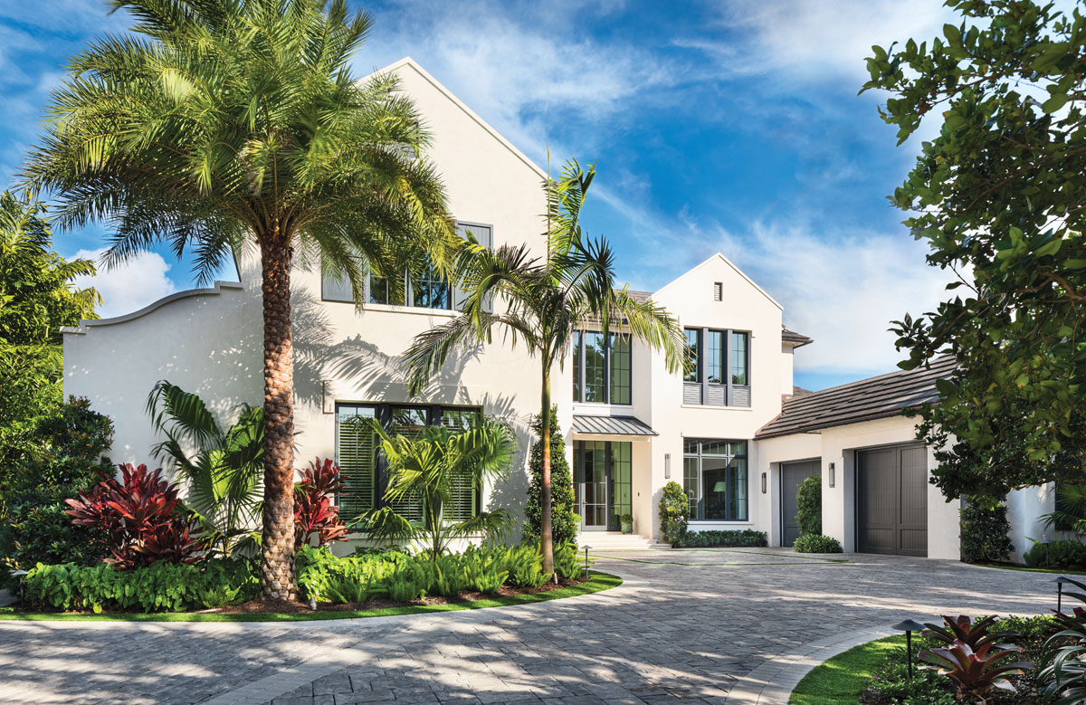 A jungle of tropical palm and banyan trees screens the entrance to the home of John and Karen Melk on Naples Bay. Architect John Cooney departed from his traditional classic approach to construct a contemporary barn idiom for his clients.