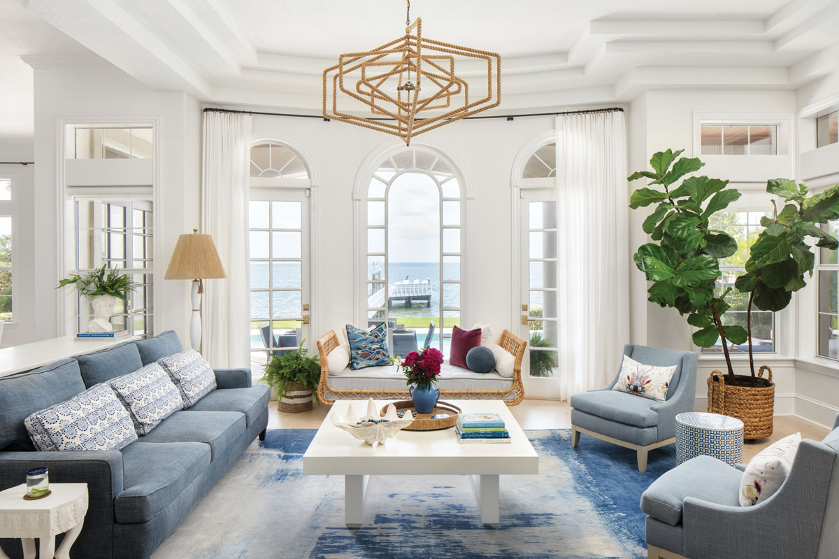 """Kravet's simple, white duck cloth frames transomed arched windows to provide the perfect backdrop for Serena & Lily's """"Avalon"""" rattan daybed that beckons lazy afternoons overlooking the shores of Tampa Bay."""