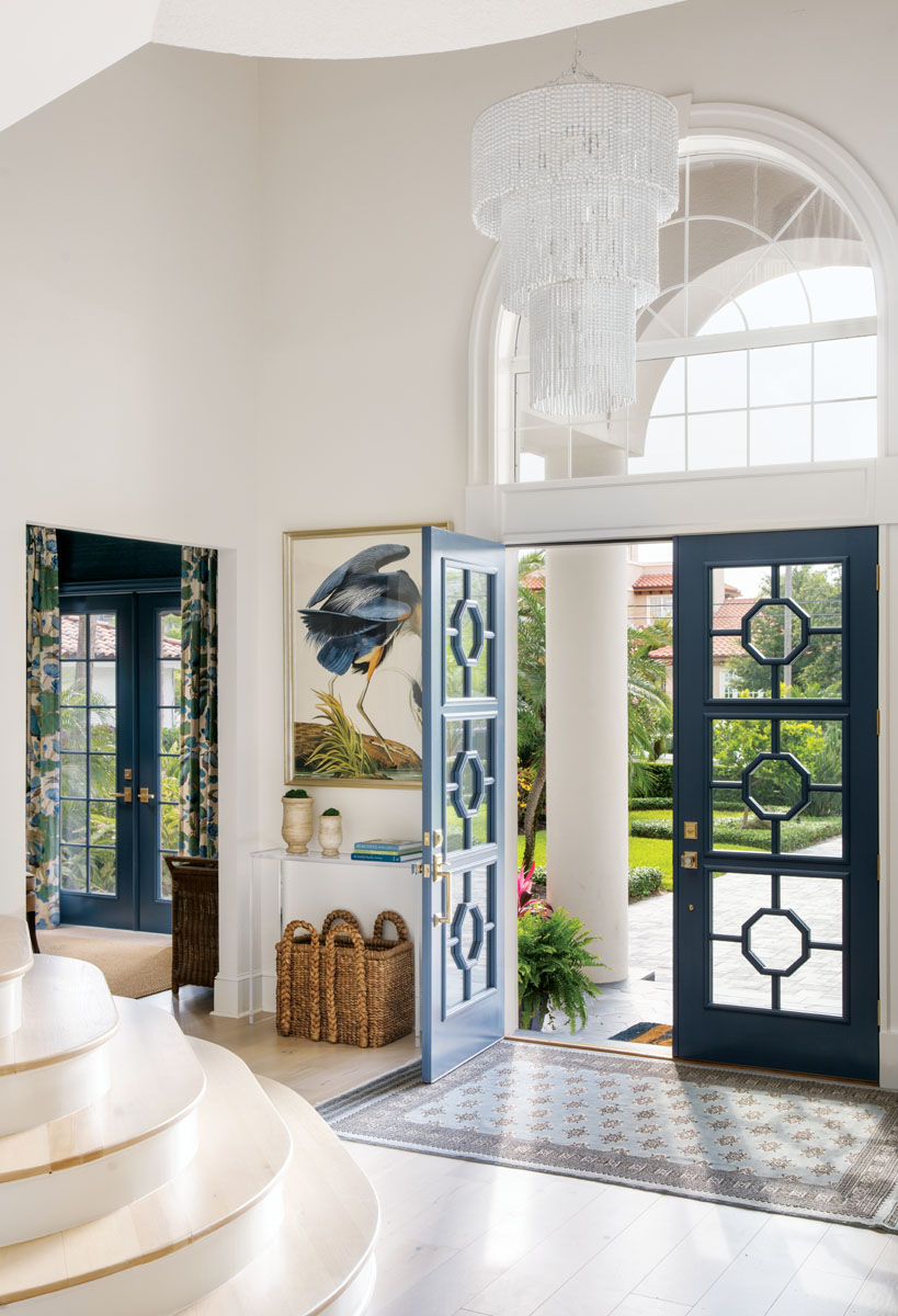 Doors Galore's panels open to the foyer, where Wendover Art's Blue Heron appears right at home. Here, a voluminous, arched transom window emboldens a coastal Mediterranean trend. The area rug, a vintage find by the designer while in Turkey, initiates the interior scheme.