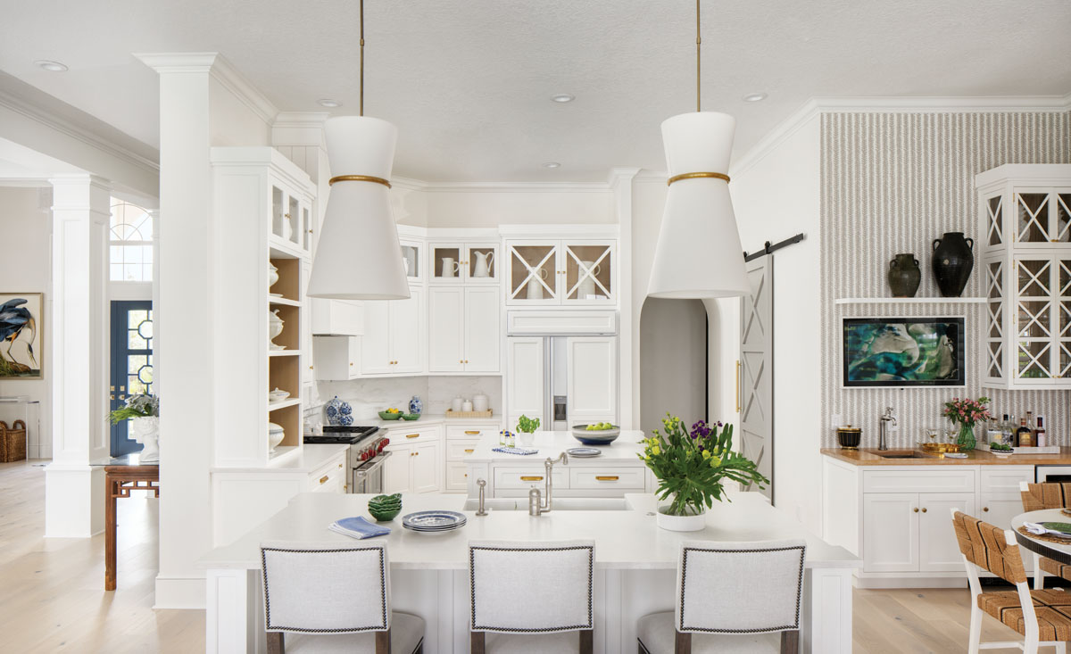 """One can't help but marvel at Circa Lighting's """"Clarkson"""" pendants, as sightlines draw the eye around the kitchen wrapped with McKenzie's crisp white cabinetry topped in quartz. The custom, gray sliding barn door by interior designer Pamela Harvey pairs with ornate brass accents and bursts of tropical hues to color the culinary space."""