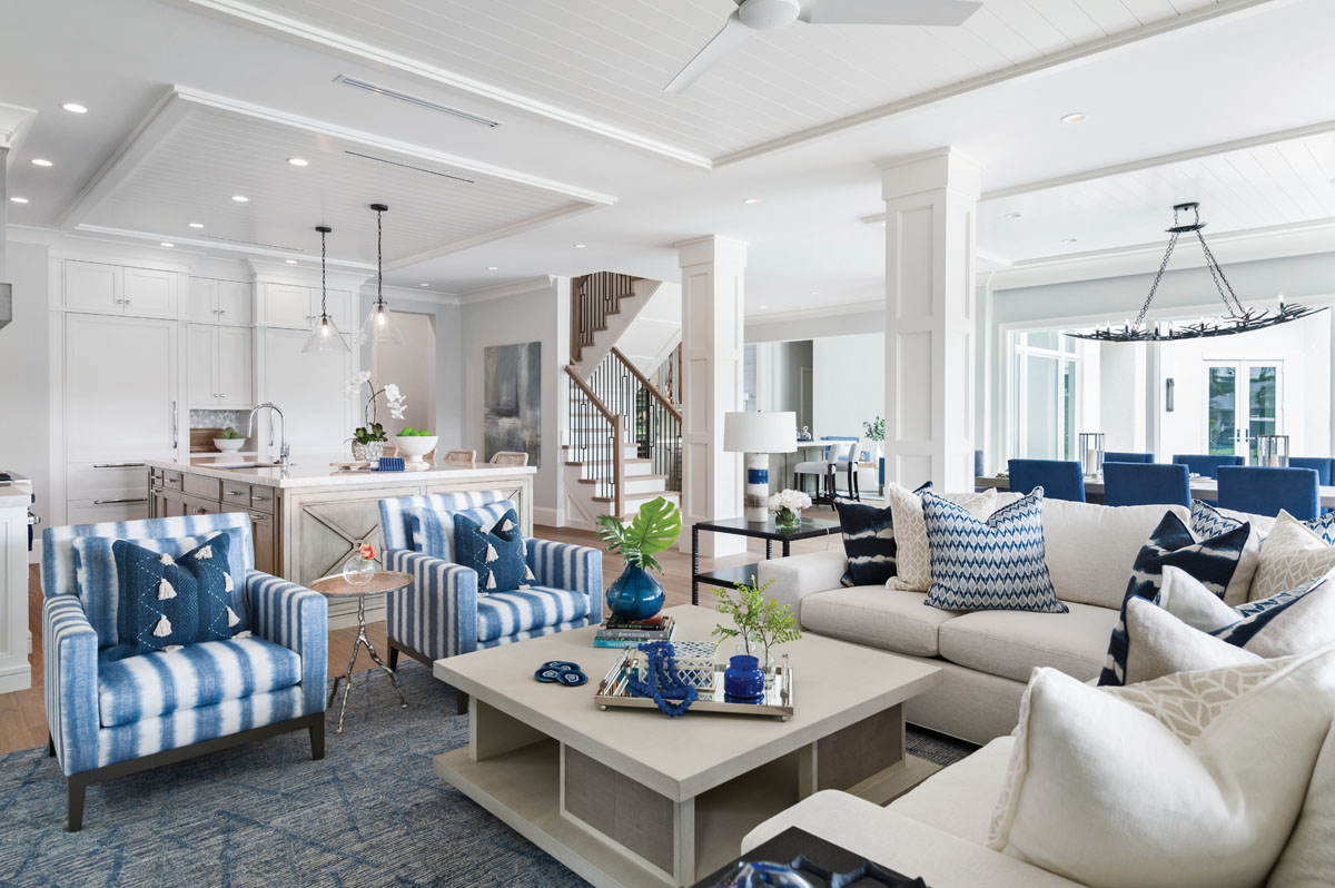 Tone-on-tone neutral colors flow into the great room, where splashes of blue are sprinkled throughout the living area. A clean-lined sectional from Theodore Alexander provides deep-seated comfort, while Burton James lounge chairs in Kravet's bold stripes pair with Arteriors' accent table that lends an organic feel.