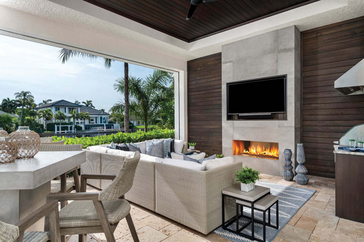 Overlooking the sparkling pool and waterways, the loggia is a comfortable conversation area with a deep-seated sectional from Kingsley Bate, nesting tables from Four Hands, and a custom fireplace.