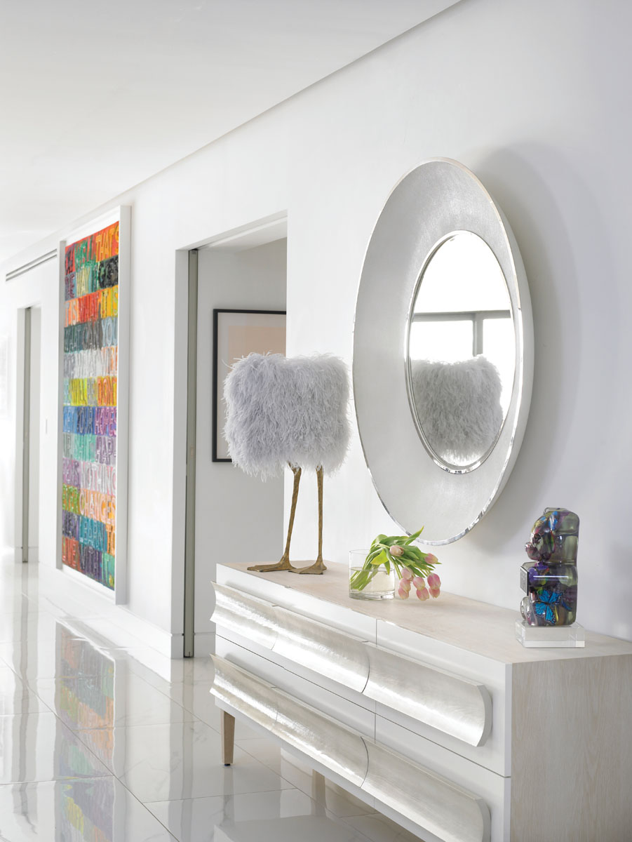 "Across the space and making quite a statement, E.G. Cody's oversized mirror edged in white shagreen captures the whimsical spirit of Porta Romana's iconic ""Duck Feet"" lamp shaded in lavender ostrich feathers."
