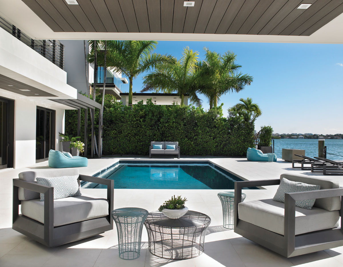 Comfortable boxy seating from Restoration Hardware pairs with the light and airy circular forms of Clima Home's ensemble of metal wire tables. Surrounded by oversized porcelain pavers, the lagoon colored pool is a smooth transition to the bay.