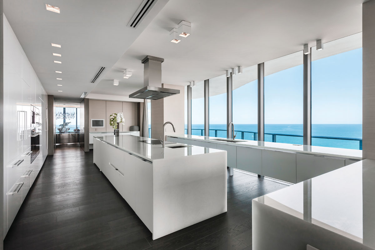 Sleek white cabinetry runs the expanse of kitchen, where a service area in the background acts as storage space or a transition area for the homeowners when entertaining guests in the dining room on one side or the wraparound balcony beyond.