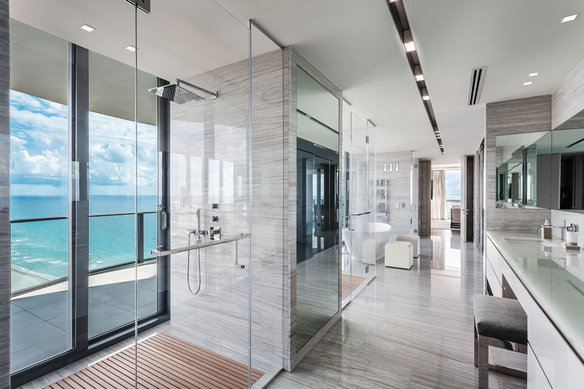 His-and-hers showers are accentuated by neutral-toned marble and an inset teak grid reminiscent of an outdoor shower. Nearby, a deep-soak tub provides the perfect spot for oceanside relaxation and rejuvenation.