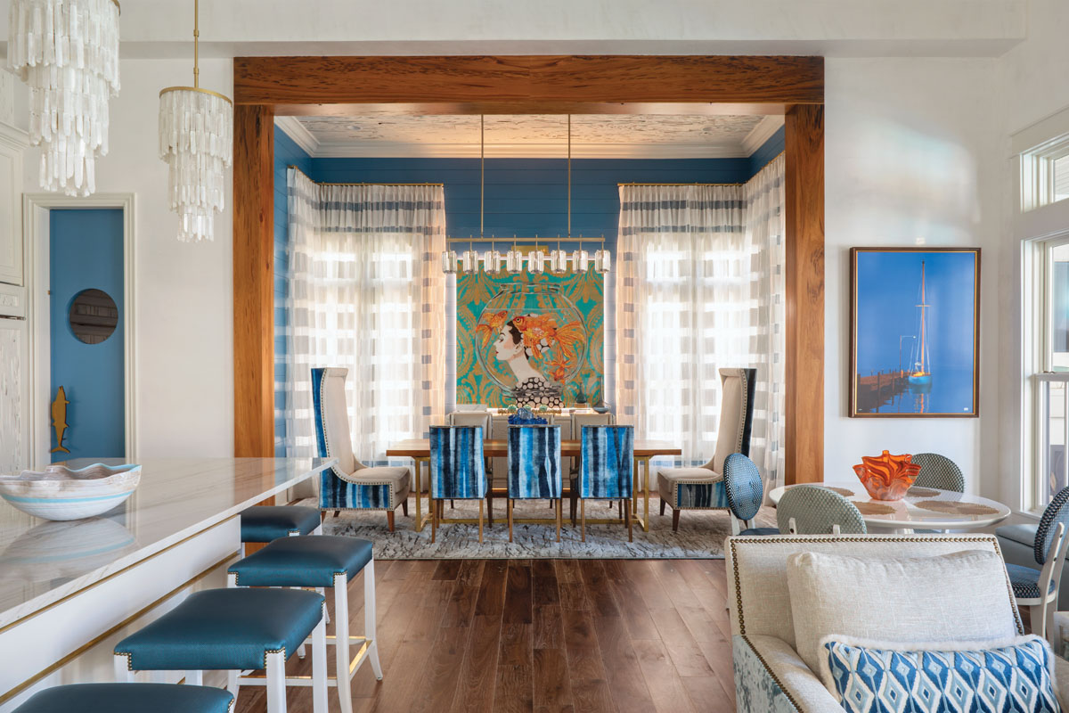 Awash in tranquil shades of blue, the dining room chairs are backed with an undulating Viridis Topaz ombre-stripe velvet. Ashley Longshore's fishbowl painting provides an eye-grabbing focal point, and linear crystal lighting floats overhead like a sparkling crown.