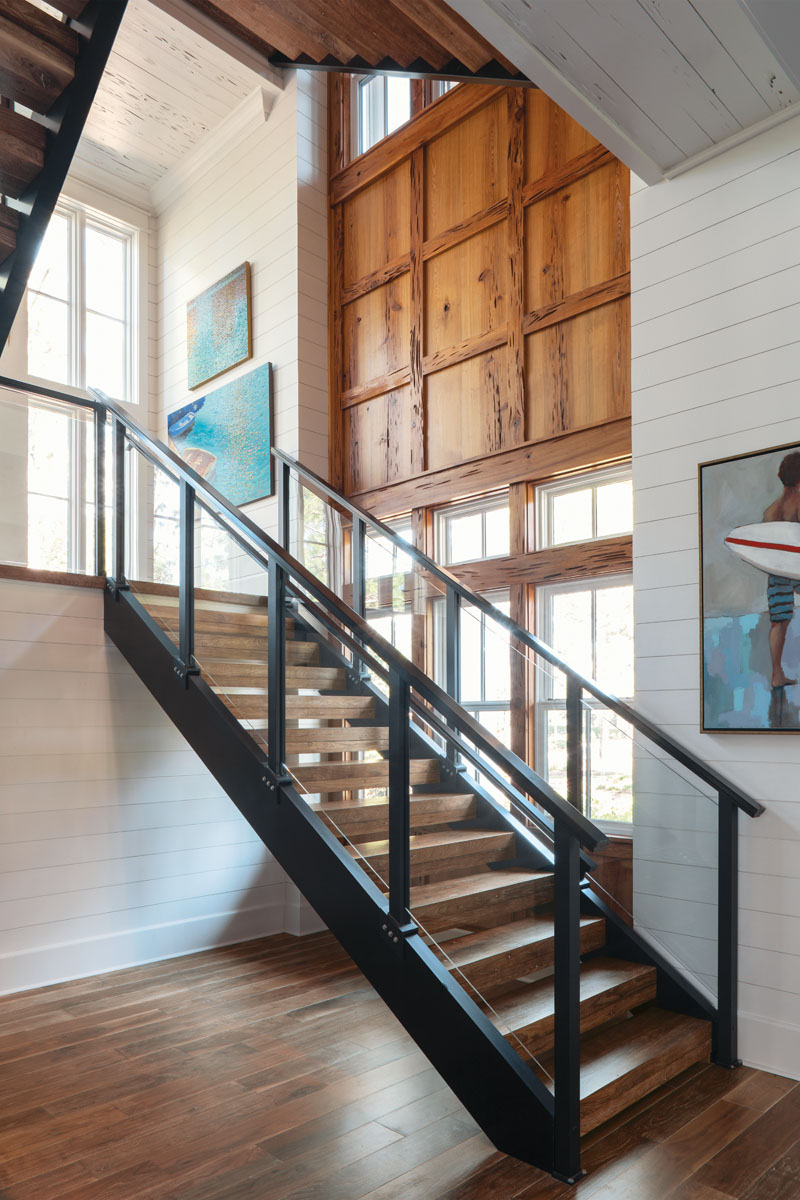 The three-story floating staircase features glass balusters for a clean, open aesthetic. Downlit hand railings lend a glow at night. Windows stretching up all three stories flood the space with natural light, and a pecky cypress-paneled wall provides texture..