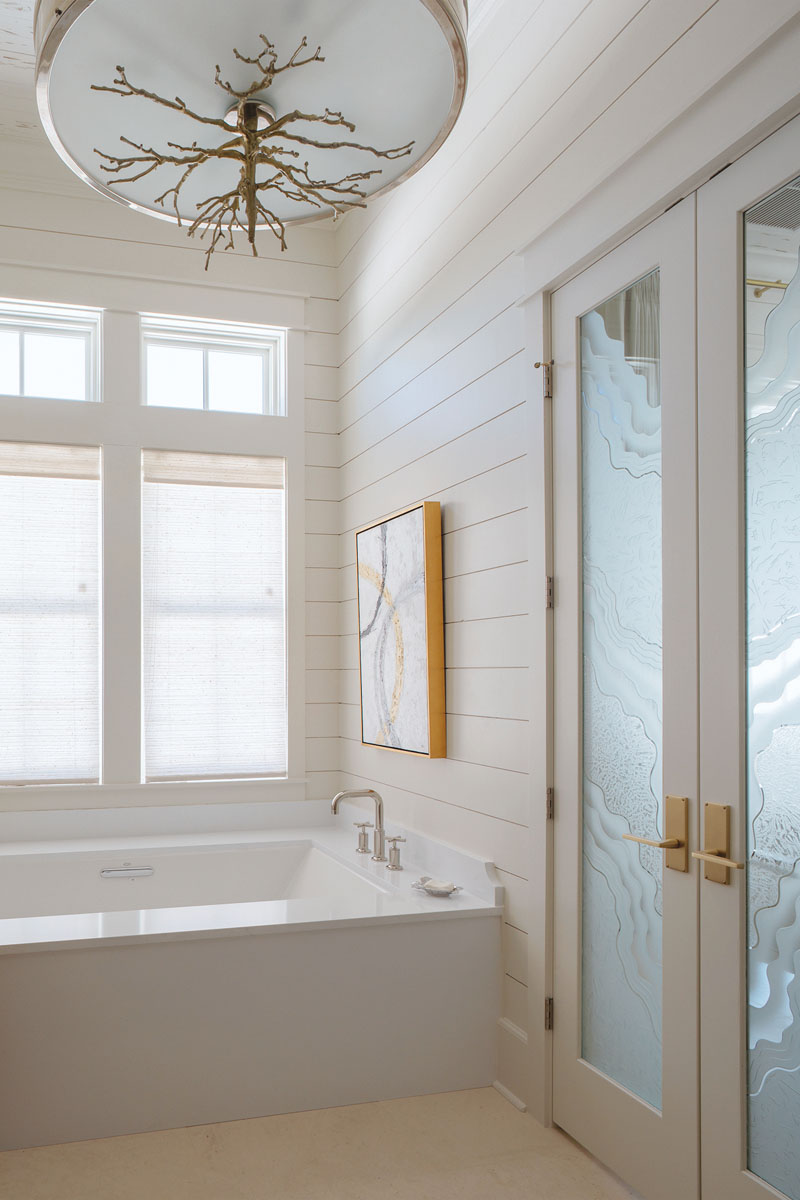 A sleek Kohler Tea-for-Two tub with polished nickel hardware keeps the master bath minimalist. Custom glass doors etched with an ocean wave embody a windswept beach aesthetic.