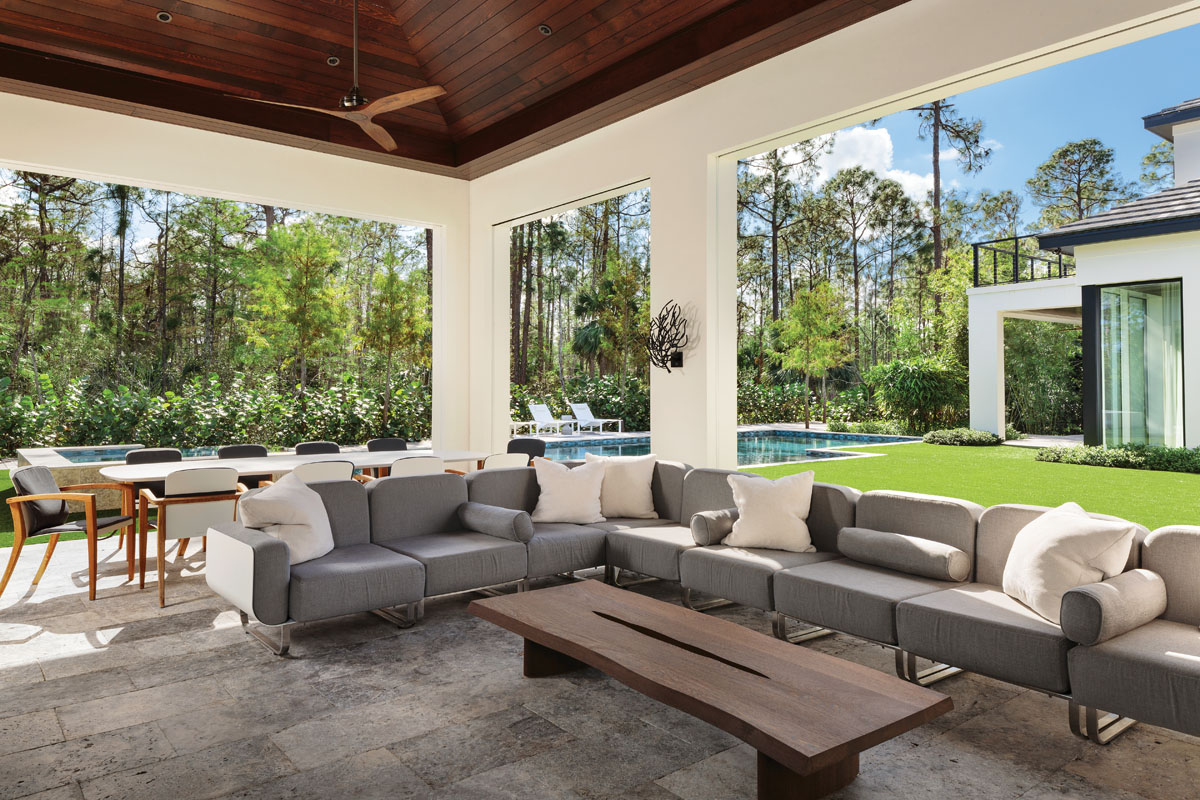 Designed to mirror the earthy color palette and organic feel of the interiors, this inviting loggia is backed by the lush Naples landscape and furnished with plush outdoor seating from Duo Designs. An expansive walnut slab coffee table from Christian Liaigre balances the long L-shape lounging sofa. Custom-designed sconces resembling tree branches cast beautiful shadows at night.