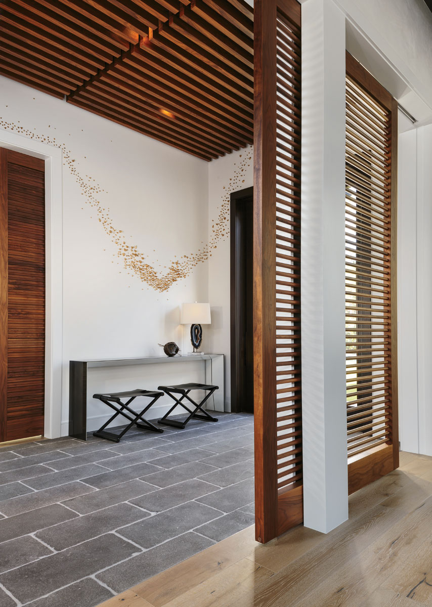 A backlit walnut slatted ceiling in the foyer offers a serene welcome. To balance the ceiling's visual appeal, a walnut dowel sliding wall provides just enough privacy for the formal living area. The compelling Swarm of Thorns wall installation was created by Naples-based artist Ran Adler.