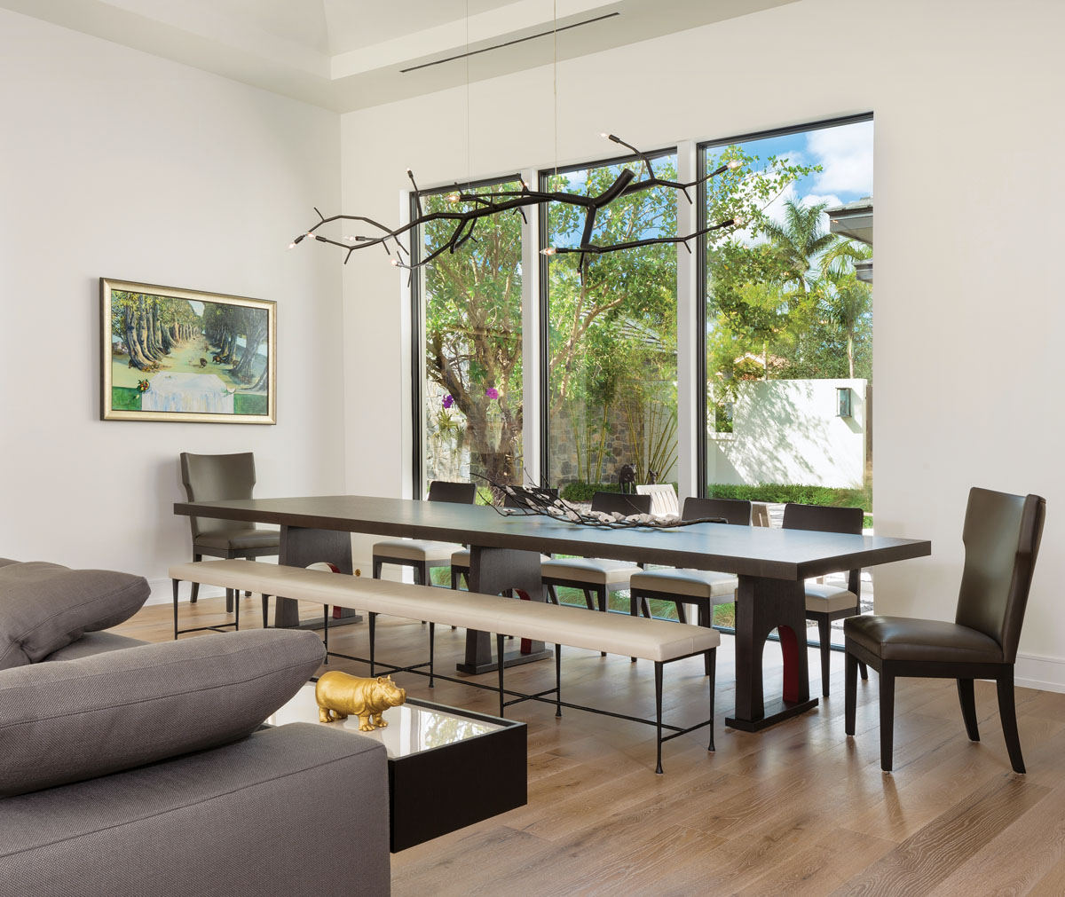 A 12-foot-long Christian Liaigre dining table provides space for large-scale entertaining yet offers intimacy for a small family. The artwork depicting a bucolic scene of a dining table set between a stand of trees was a wedding gift. Hanging overhead, a custom chandelier from CP Lighting suggests a modern reflection of the organic shapes viewed outside the floor-to-ceiling windows.