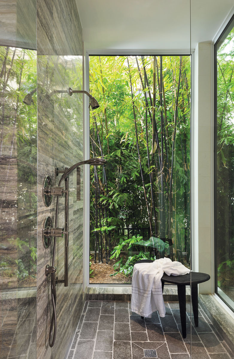 In the master bath, floor-to-ceiling glass offers the sense of showering in a rainforest.