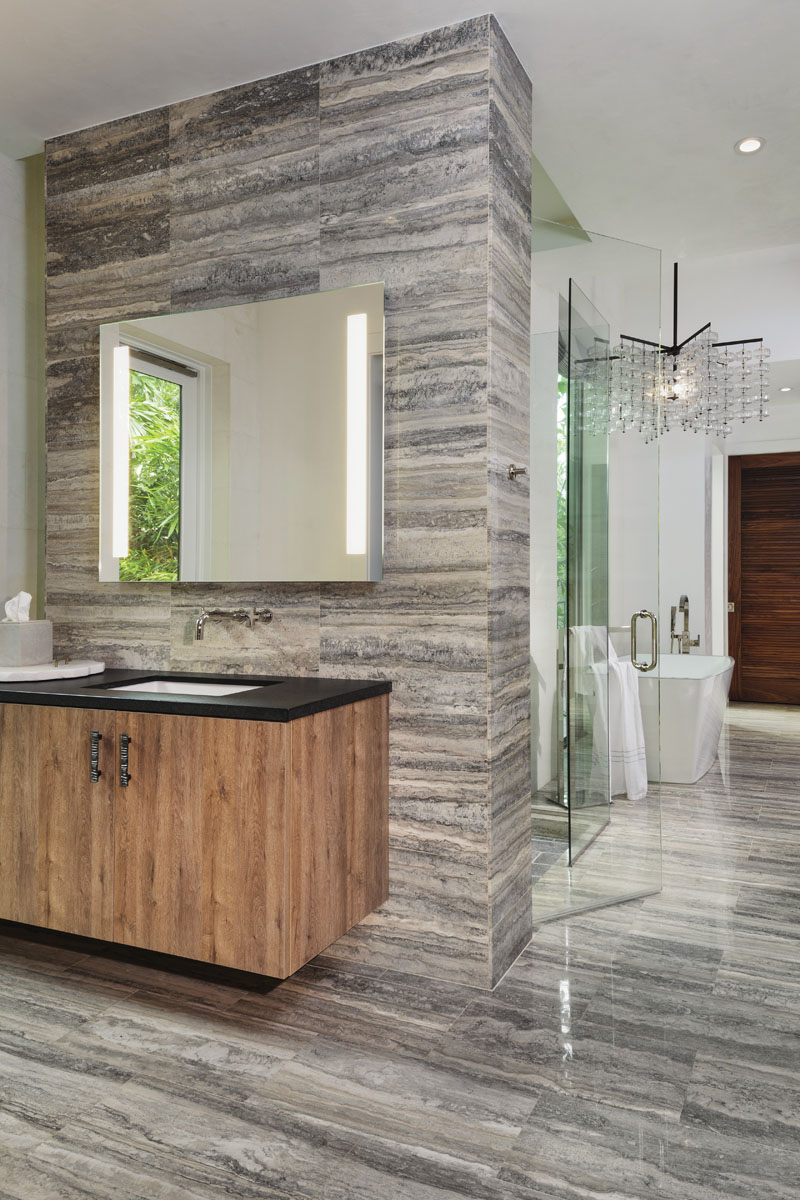 Black travertine from Naples Stoneworks clads the floors, walls and front of the vanity, reflecting the striations from the black bamboo scene just beyond the windows. A vintage 1920s chandelier from the Berlin Opera House punctuates the space in grand style.