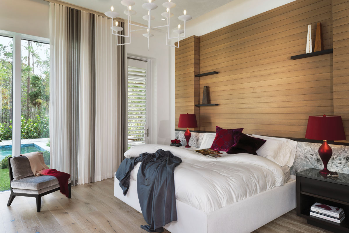 In the master bedroom, a headboard cushioned in marble-motif velvet by Michael Schmidt complements the sleek oak wall paneling. Marble-top nightstands accented with red Murano glass lamps by John Hutton flank the bed, and a white gesso-plaster chandelier from Luxe Lighting lends understated glamour.