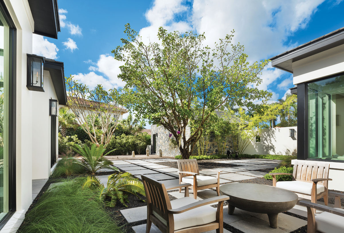 The front courtyard pays homage to a graceful silk floss tree. The Japanese sand garden in the far corner balances a stone-clad wall that surrounds a separate garage structure.