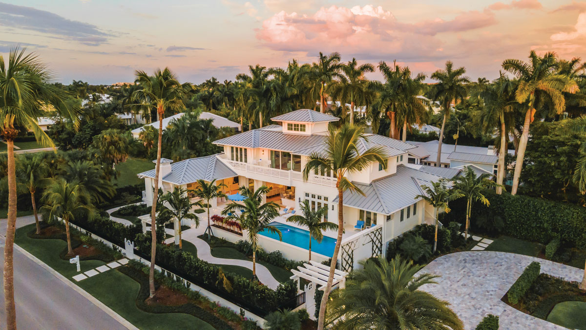 This London Bay Homes custom masterpiece was designed to capture Gulf sunsets and fit its surroundings as though it belonged in Old Naples for decades. A grand pedestrian arrival leads guests through trellises, lush landscaping, and an S-curve walkway to a pergola entrance and the home's outdoor living space.