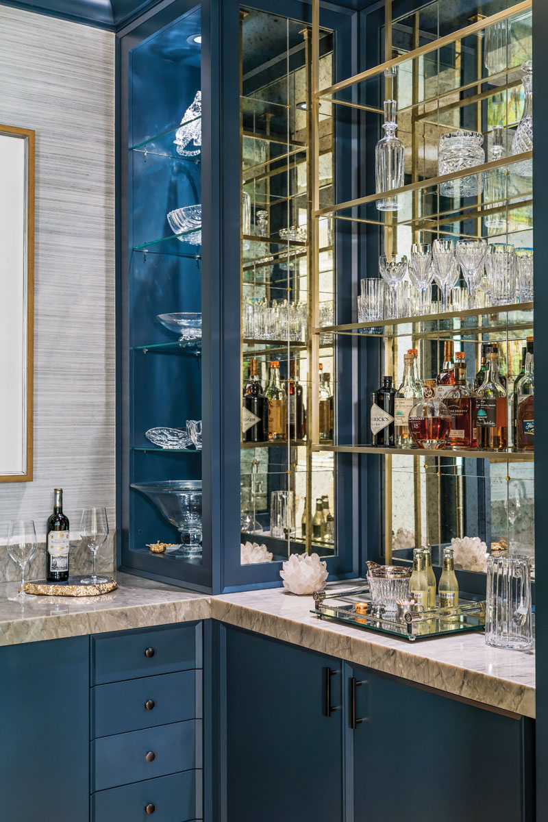 The vivid blue three-sided bar across from the home's entrance features a Sea Pearl Venato countertop fabricated by Naples Stone Works, a hidden, under-counter refrigerator, and AlliKriste cabinetry to display the client's own crystal stemware.
