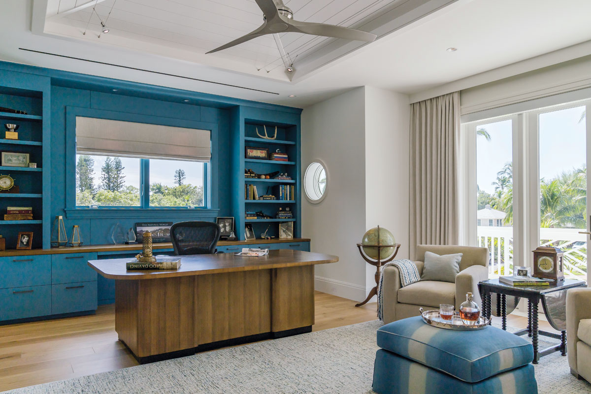 The owner's office centers around his father's refinished wood desk, flanked by deep turquoise AlliKriste wall cabinetry that exhibits treasured family heirlooms. Lee Industries Club chairs beckon guests into a conversational corner, while the client's ottoman, reupholstered in Lee Jofa fabric by Michael Schmidt Custom Interiors ties the bold blue hue into the predominantly off-white room.