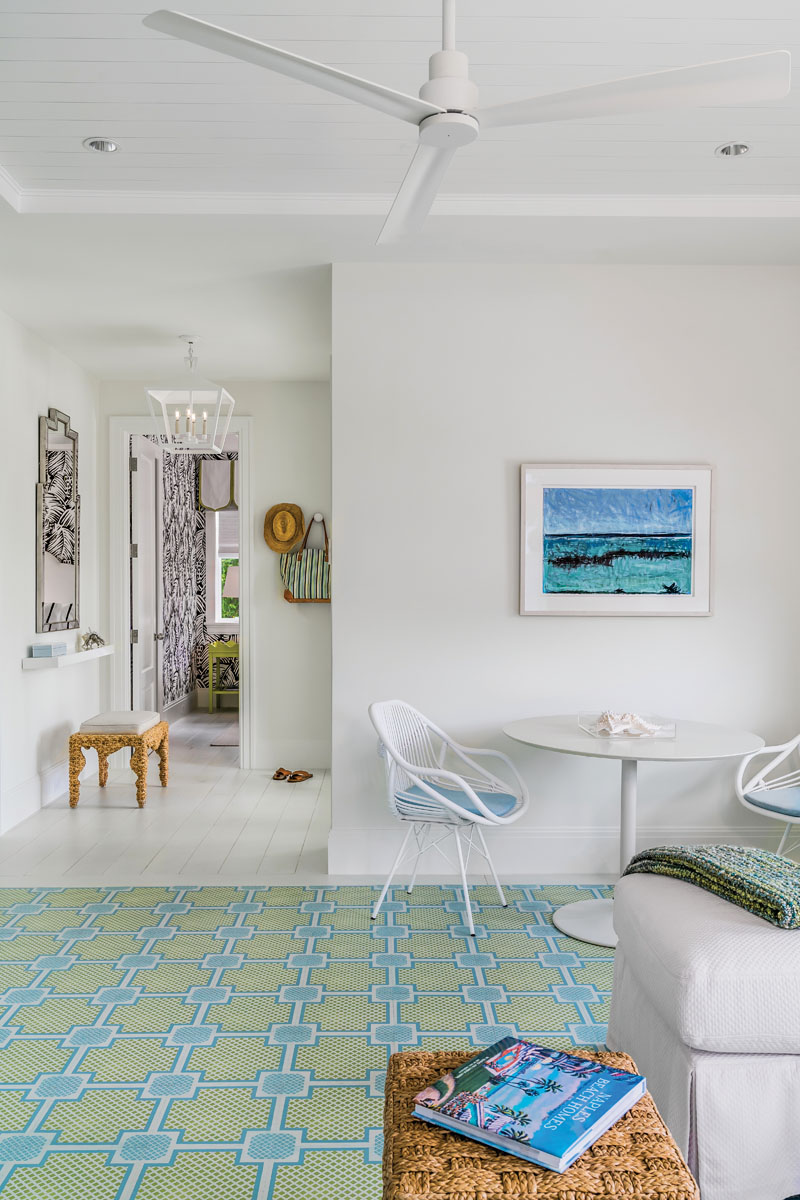 """Lucky is the guest ensconced in this suite, with its 12x12 Mirth Studio wood floor, custom-painted in a green and turquoise Old Florida trellis pattern – a nod to old Palm Beach style. Simple furnishings, including David Francis Furniture chairs surround the client's own CB2 pedestal table, wicker side table, bench, and mirror. A Chaddock lighting pendant leads into a powder room covered in black and white Hermes """"Feuillage"""" palm frond design."""