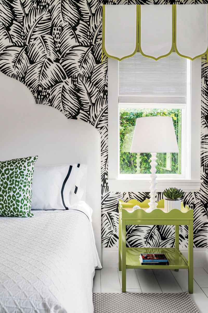 """raphic black and white Hermes """"Feuillage"""" palm frond wall coverings get an unexpected pop of green with an Oomph Home side table in this fanciful guest bedroom. Crisp white linens beckon under a Jennifer Stevens custom-designed headboard fabricated by Michael Schmidt Custom Interiors."""
