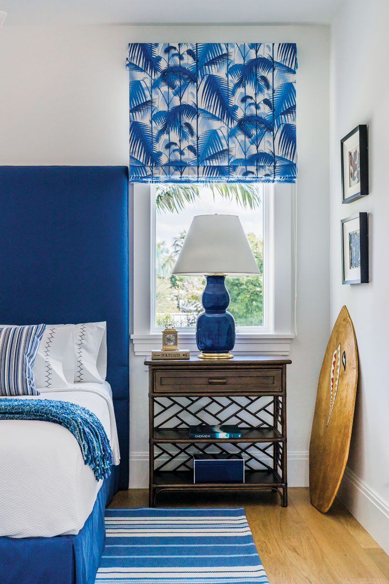 """Lee Jofa """"Palm Jungle"""" fabric window coverings by Michael Schmidt Custom Interiors create a cheerful guestroom vibe, made cooler by the vintage wood boogie board propped against a corner wall. A tall, deep blue Vanguard Furniture headboard is accented by a David Francis Furniture side table and the client's own blue striped area rug."""