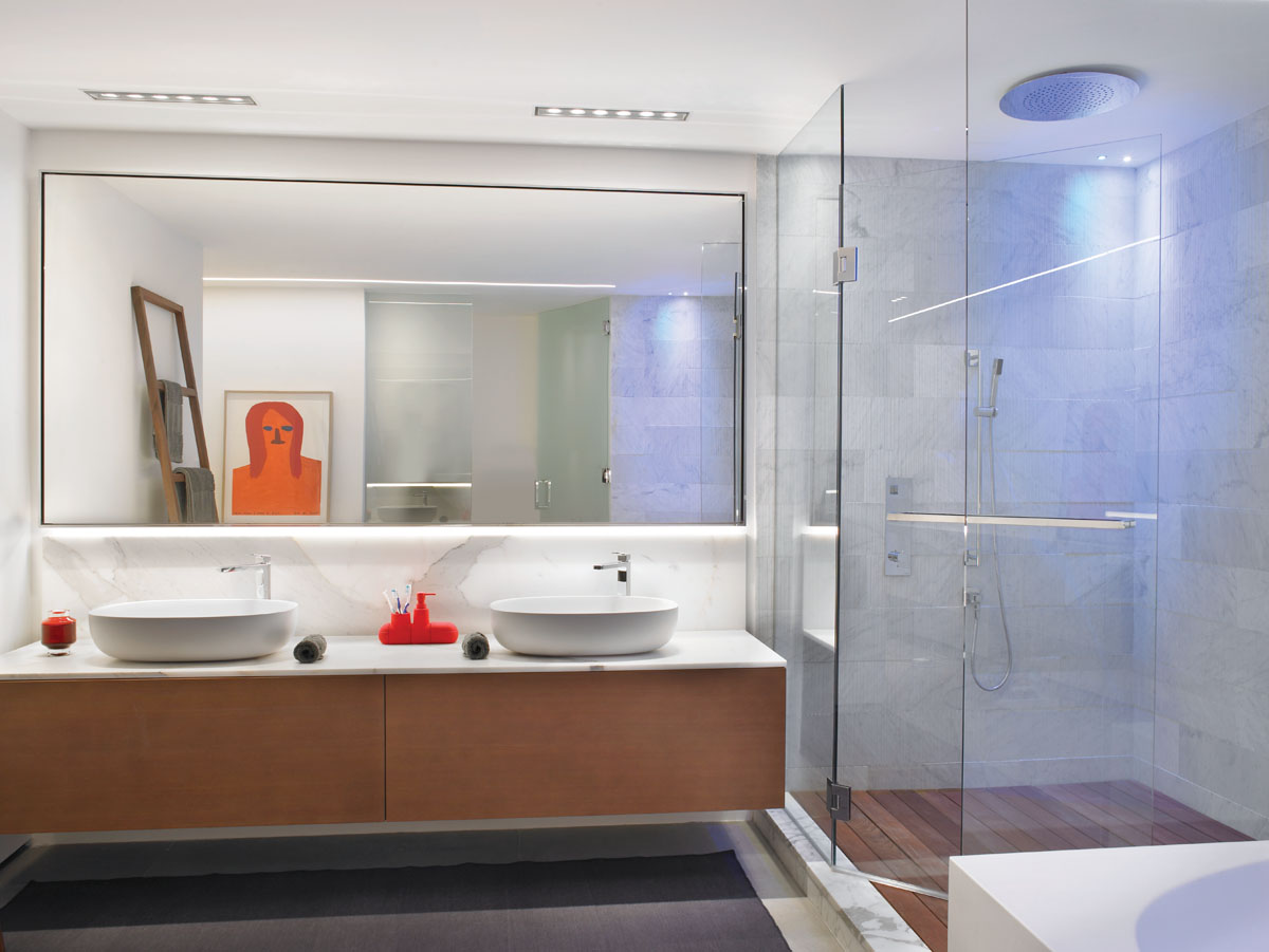 As part of his lighting design in the master bath, Glottman added a cool blue light to the rain shower for added contrast. Reminiscent of a dock, the shower's wood flooring offers a Balinese touch. The lacquer Rexa vanities and visual artist David Shrigley's piece finish off the private space.