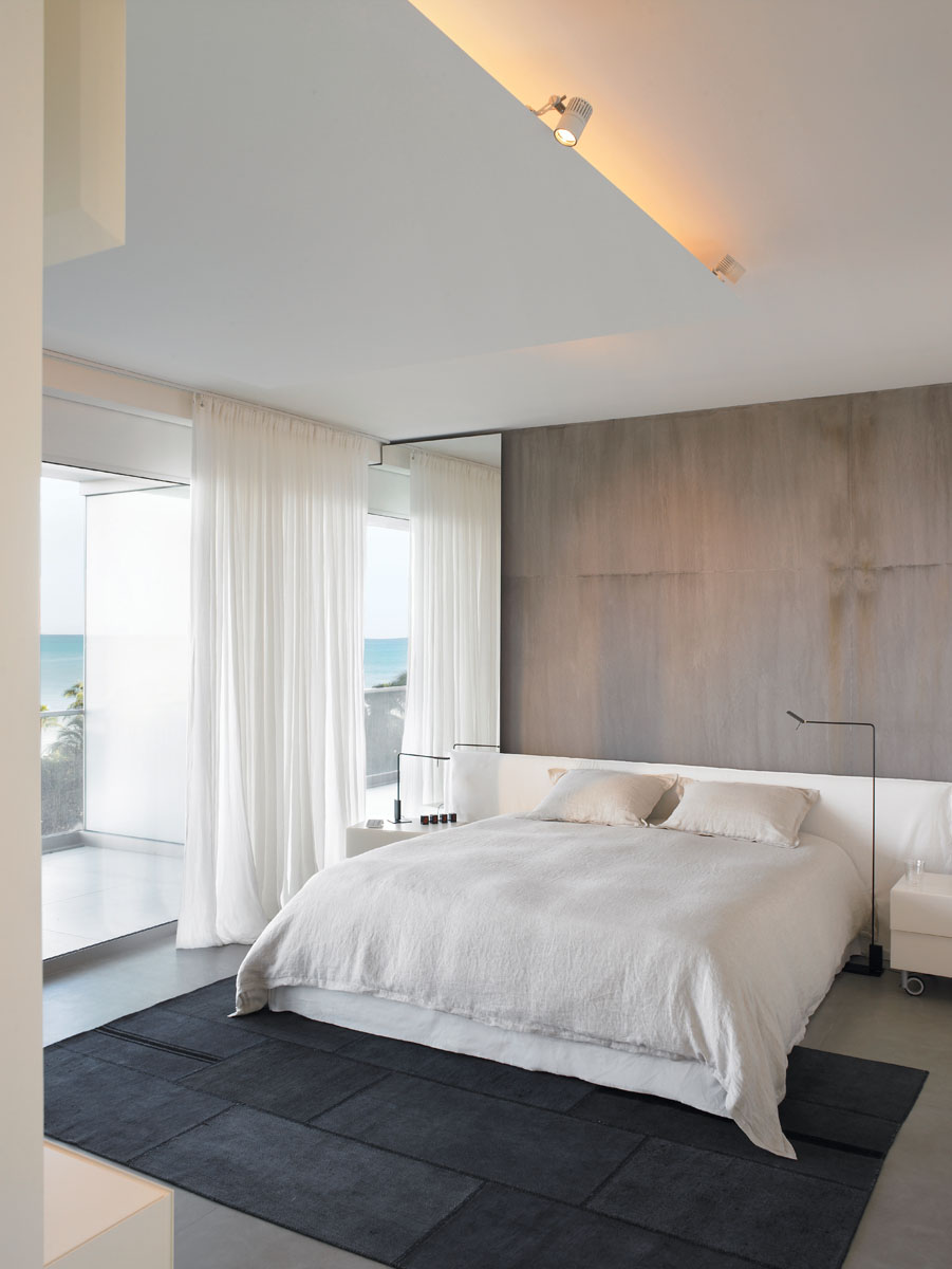 Gervasoni's linen-clad headboard lines the master bedroom's focal wall in complement to the crisp, white linen sheers, while Viabizzuno reading lamps, a charcoal gray kilim area rug and the concrete gray resin wall add contrast.