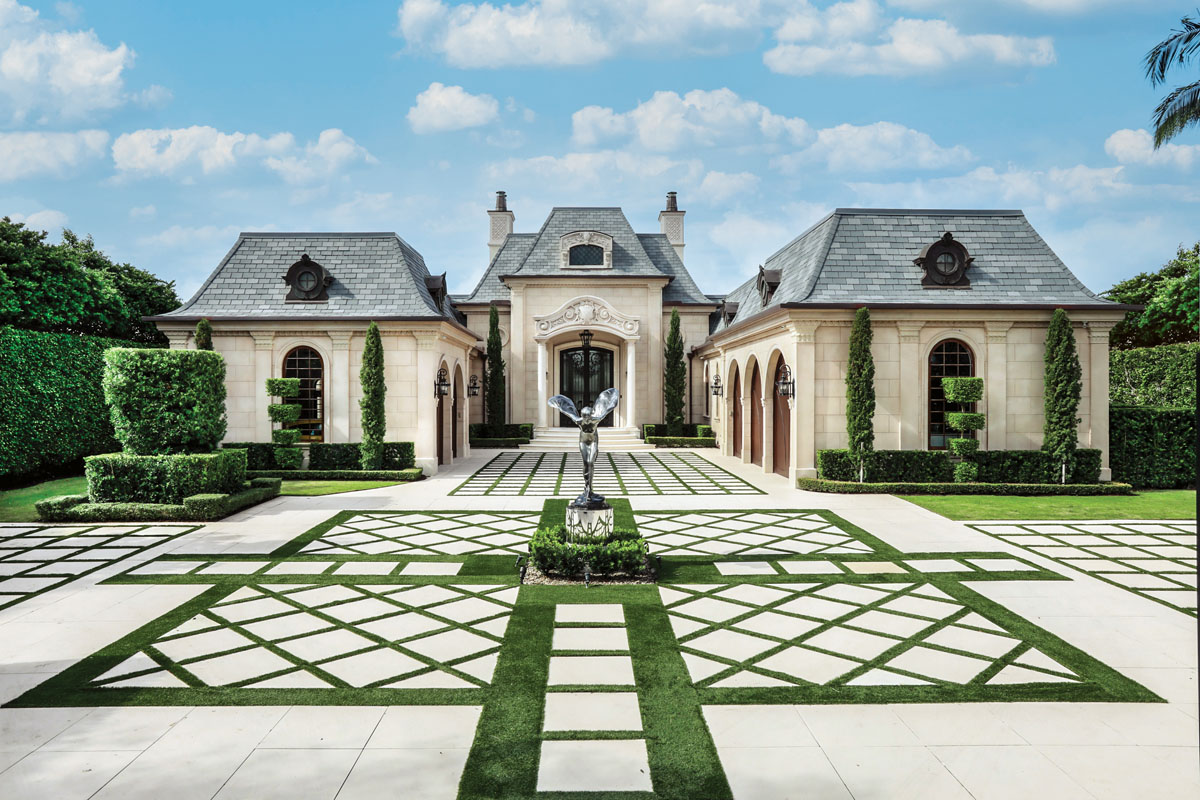 A geometric-patterned, European-style auto court leading to two ornate stone garage wings defines the entrance of this French Renaissance–style estate in Jupiter. DesRosiers-Markovitz_FD31-1APhoto by Jason Nuttle Photography