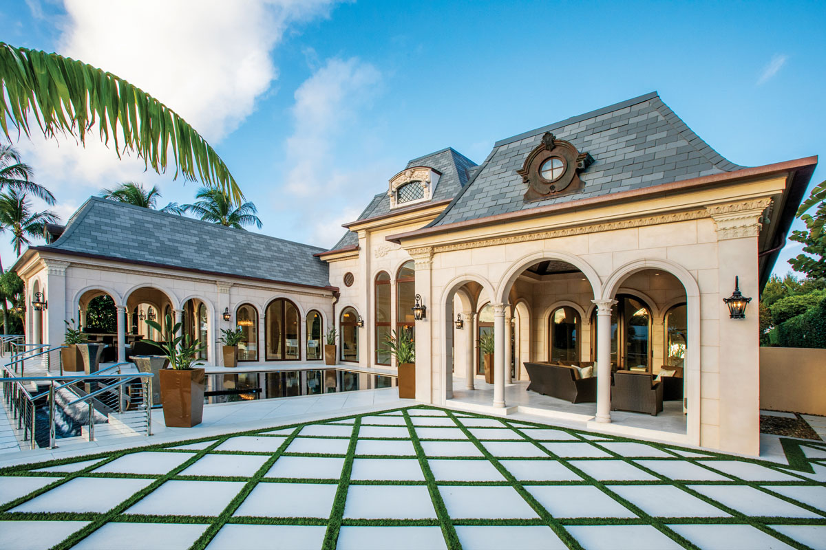 The geometric-patterned, grass-and-stone landscape is carried from the entrance to two patios, an outdoor kitchen, and the area surrounding the azure mosaic-tile pool. DesRosiers-Markovitz_FD31-1CPhoto by Jason Nuttle Photography