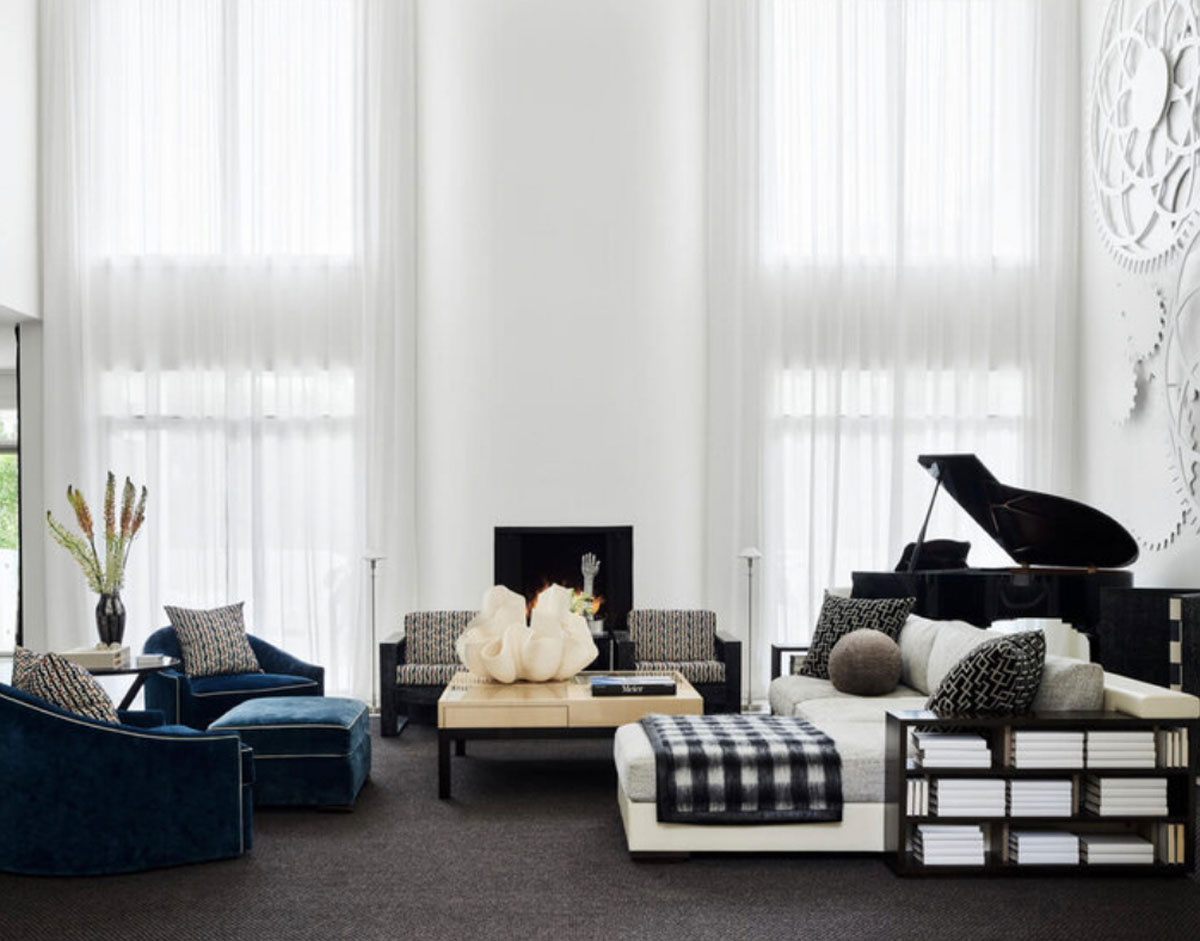 A soaring contemporary living room in Nashville features a large art installation of wooden gears purchased at the renowned Swan Ball benefiting the Cheekwood Botanical Garden. Miles of white cotton voile from Rubelli covers the windows. All is grounded by a sea of charcoal broadloom from Stark Carpet. Photo: Douglas Friedman