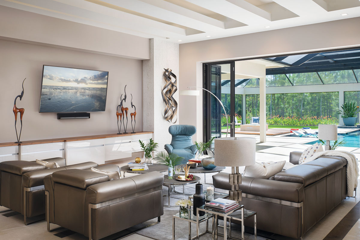 "The room's brown leather furniture has an iridescence to it, Davenport says, ""so it goes from sort of a blah brown to a sexy shimmer, which is a little bit edgy."" The reclining sofa's hue complements the inlaid wood in the shellstone floor."